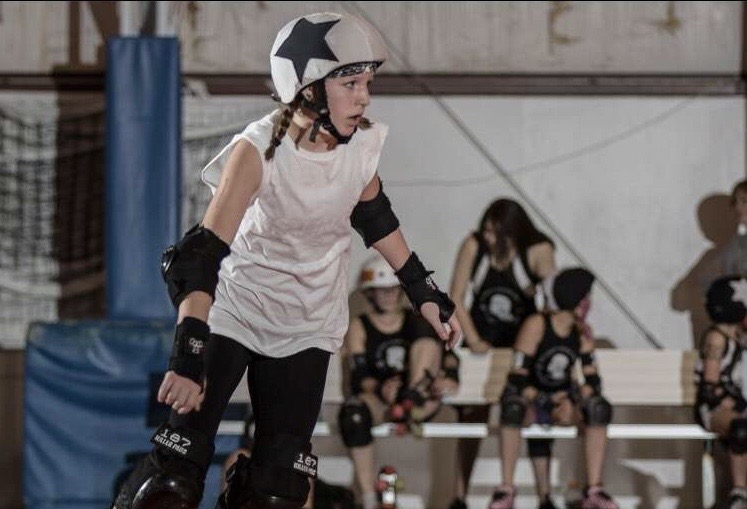 Turner races around the track, trying to score points for her team by lapping opponents. She plays jammer and blocker.