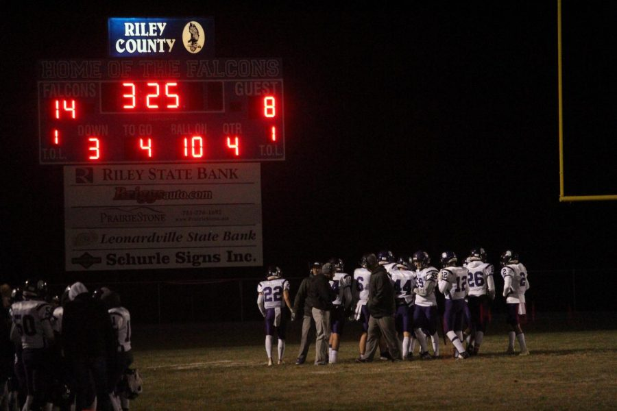 The trojan football team huddles together at a timeout during the game at Riley County.