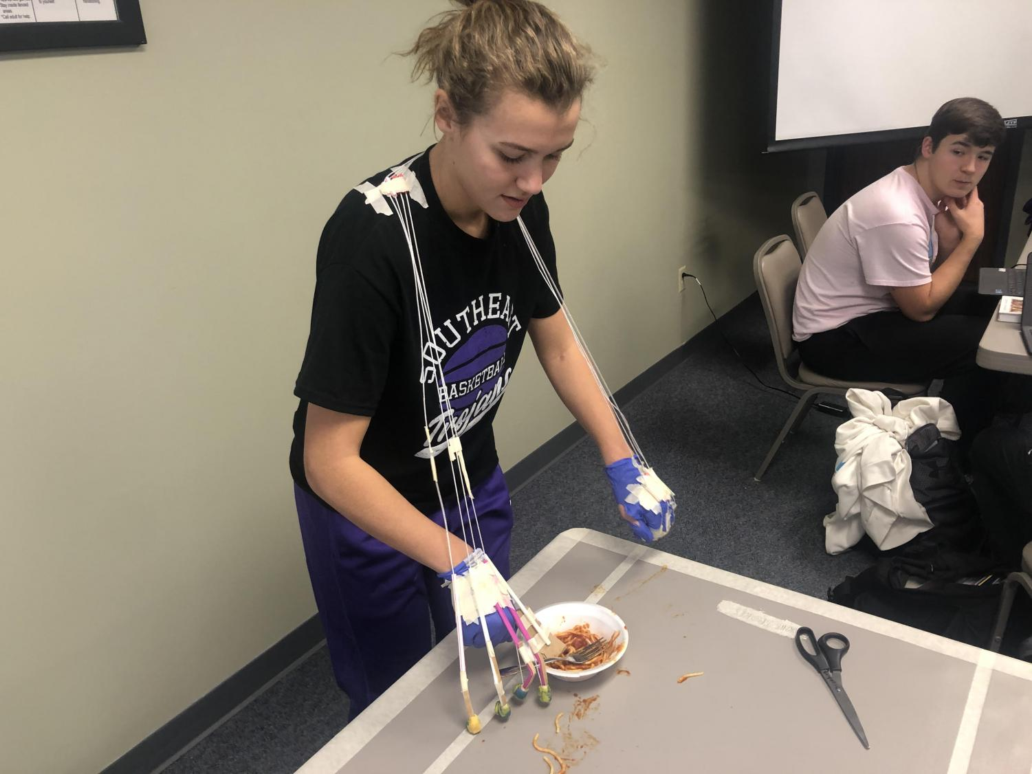 Madeline Blake tries to eat spaghetti with her prosthetic hand that she made in Anatomy and Physiology. The class did this project in the district office while they couldn't be in the classroom.