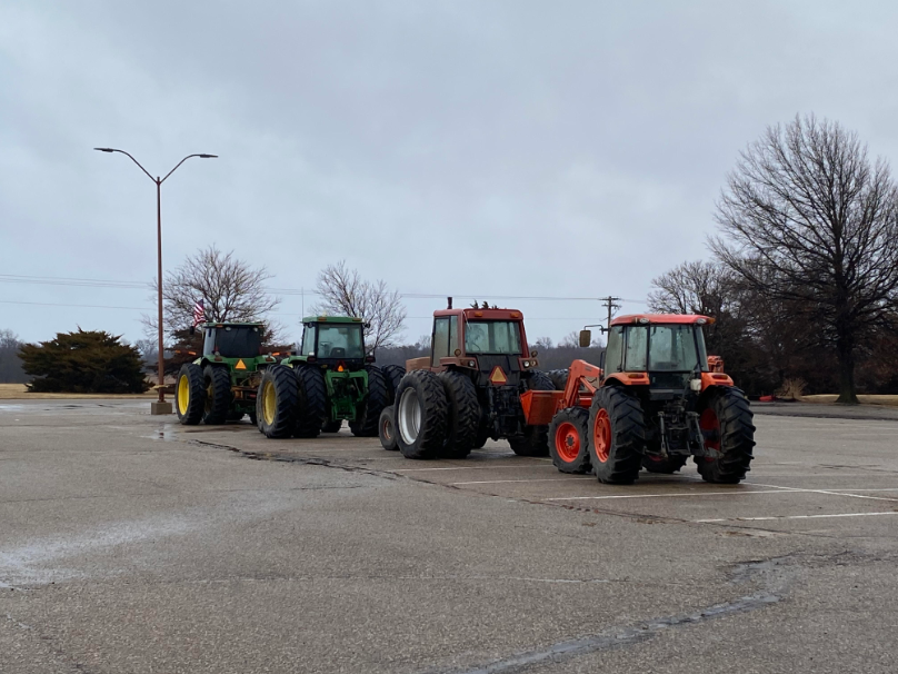 Four+tractors+that+were+driven+to+school.+They+were+parked+outside+of+the+school+on+Monday+morning.