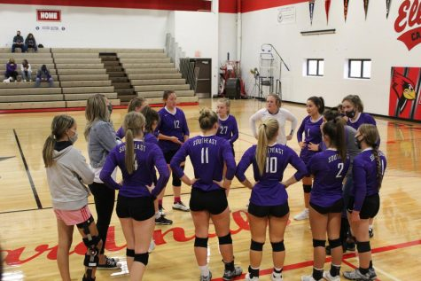 Varsity girls huddle up between sets.